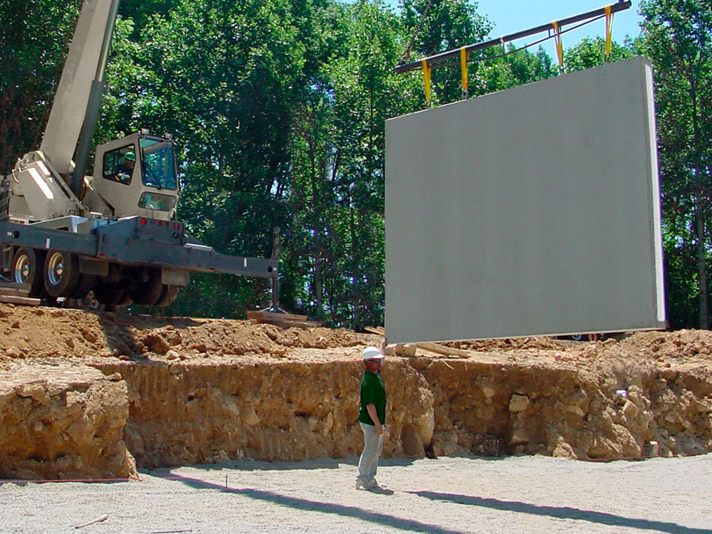 precast wall suspended over basemnt prep area